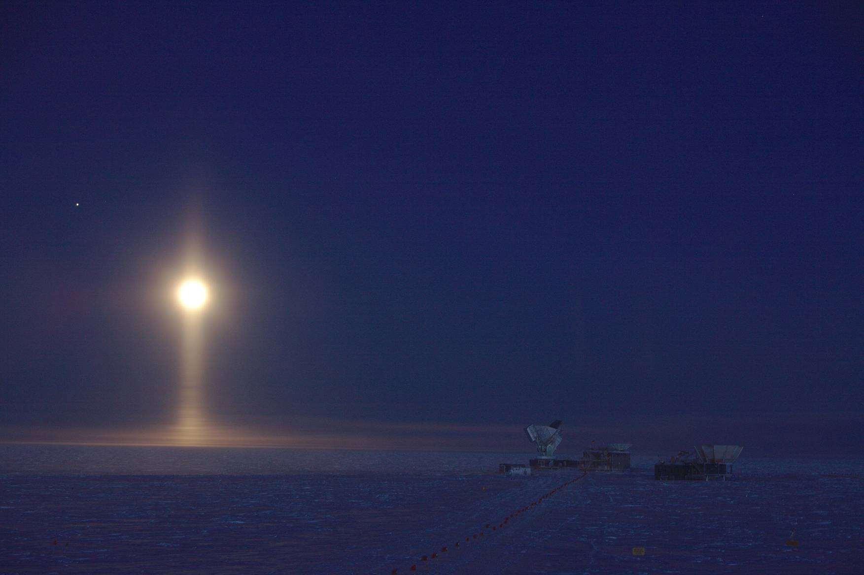 April 2017: The South Pole Telescope during EHT observations. Ice crystals in the atmosphere create a light pillar underneath the Full Moon. The bright speck left of the Moon is Jupiter.