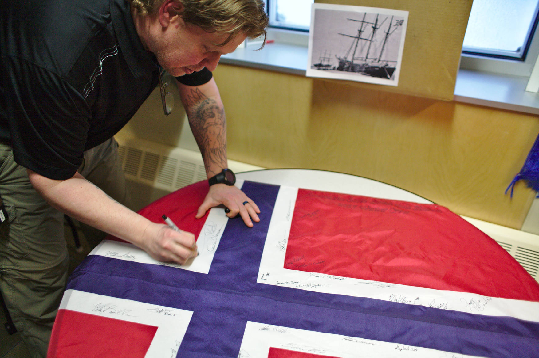 The Norwegian flag was signed by the station population. It will be taken to the polar exploration ship <em>Fram</em>, in commemoration of her use on Amundsen's 1910-12 south pole expedition (picture in the background).